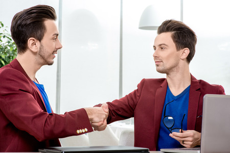 Two succesfull brothers twins handshaking at the office photo