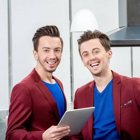 Two brothers twins restaurateurs in red jackets working with tablet at the restaurant. Family business photo