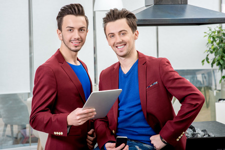 restaurateur: Two brothers twins restaurateurs in red jackets working with tablet at the restaurant. Family business