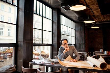 Arquitecto creativo pensando en los grandes dibujos en la oficina desván oscuro o café. Plan general con ventanas