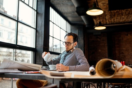 drafting table: Creative architect drinking coffee and working with the big drawings in the dark loft office or cafe Stock Photo