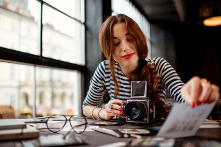 format: Young woman photographer looking at the printed photos with old 6x6 frame camera sitting in the cafe with loft design interior Stock Photo