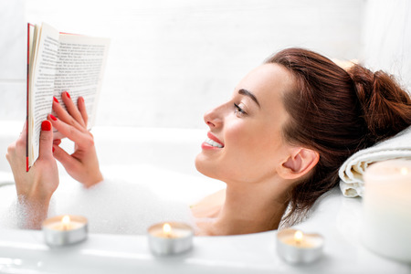 Young woman reading book while lying in the bath with foam and candles Stock Photo