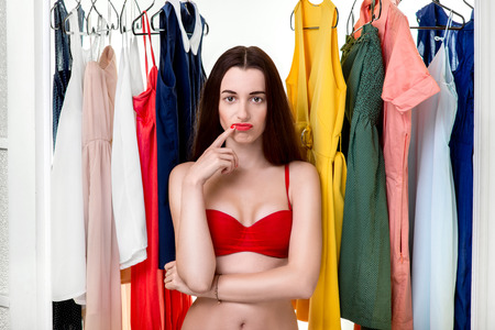 Young woman in underwear thinking what dress to wear in front of the clothes in wardrobe. Nothing to wear concept photo