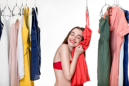 Young woman in underwear looking through her wardrobe and choosing dress to wear photo