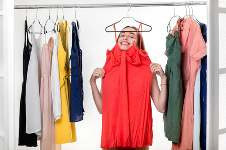 checkroom: Young happy woman dressed in underwear trying on new dress to wear in the wardrobe