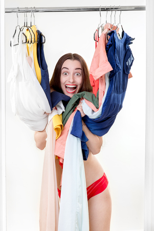 Young happy woman looking through her wardrobe choosing dress to wear photo
