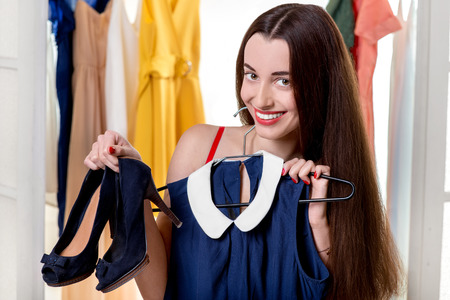 checkroom: Young happy woman trying on new blue dress and shoes to wear in the wardrobe
