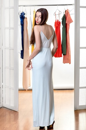 checkroom: Young happy woman trying on new dress to wear in front of the wardrobe