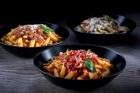 pasta: Three different pasta on wooden table with dark background