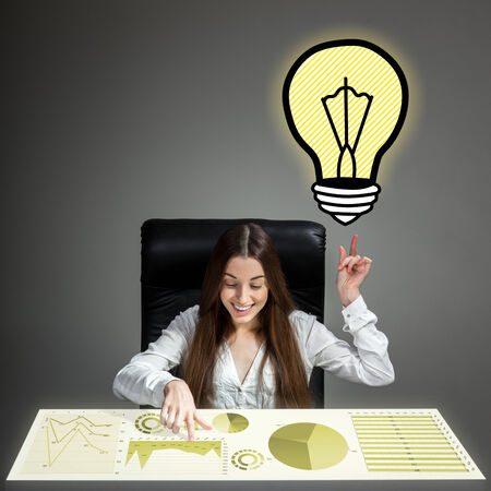 inventive: Young inventive woman having idea analyzing business plan or business calculations Stock Photo
