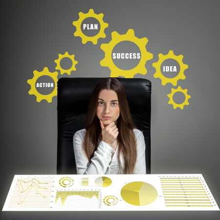 inventive: Young inventive woman thinking and analyzing business plan or business calculations Stock Photo
