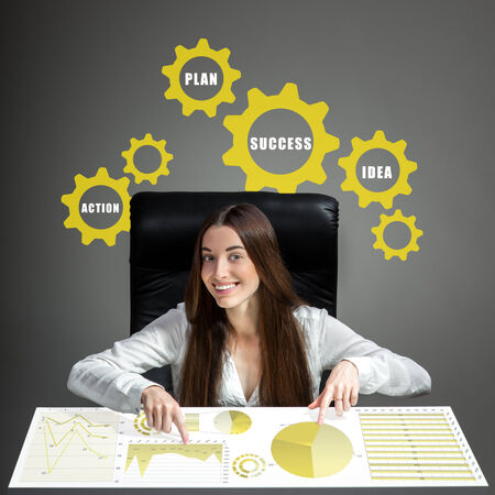 inventive: Young inventive woman analyzing business plan or business calculations