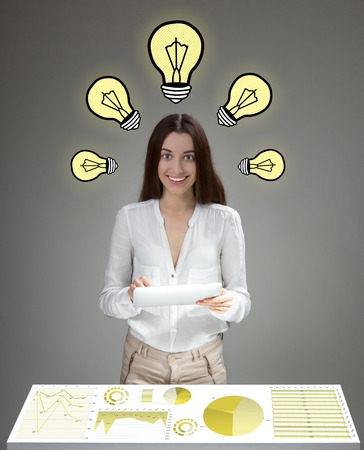 inventive: Young inventive woman having ideas analyzing business plan with digital tablet and big table screen