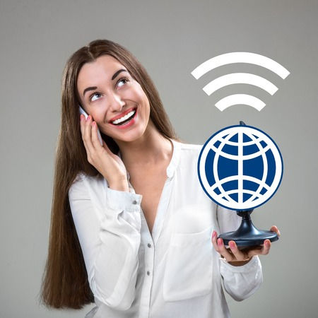 intercommunication: Young and smiling woman talking by mobile phone worldwide with graphic globe in studio Stock Photo