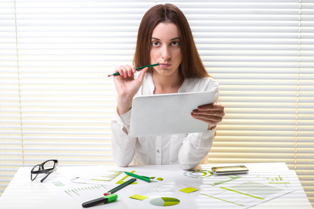 economist: Young tired woman economist working with paper graphics, digital tablet and smart phone