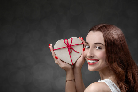 Happy and smiling young woman holding heart box with candies on grey background. Happy valentines gift concept photo