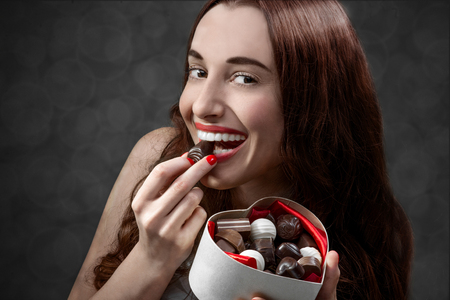 chocolate background: Happy and joyful young woman holding heart box with candies and eating them on grey background. Happy valentines gift concept Stock Photo