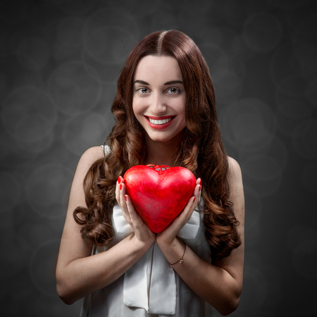 Happy and joyful young woman holding red heart on grey background in studio. Happy valentines greeting concept photo