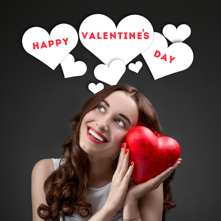 Happy and joyful young woman holding red heart on grey background with graphic hearts. Happy valentines greeting concept photo
