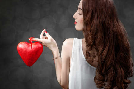 Woman holding red heart on grey background in studio, back view. Happy valentines greeting concept photo