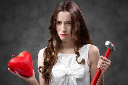 Upset woman holding broken heart and hammer on grey background. Failed relationship concept