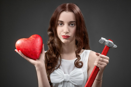 breakup: Upset woman holding broken heart and hammer on grey background. Failed relationship concept