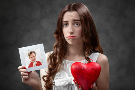 Upset woman holding photo card with boyfriend and broken heart. Failed relationship concept photo