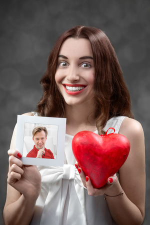 Woman falling in love holds heart and boyfriend photo in studio photo