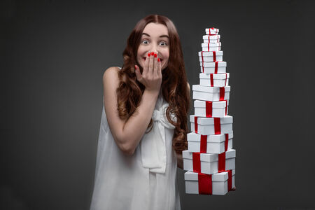 stacks: Young and excited woman with high hill of present boxes on her birthday or Valentines day in studio