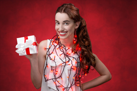 Happy and smiling young woman holding present box on the red background. Happy valentines gift concept photo