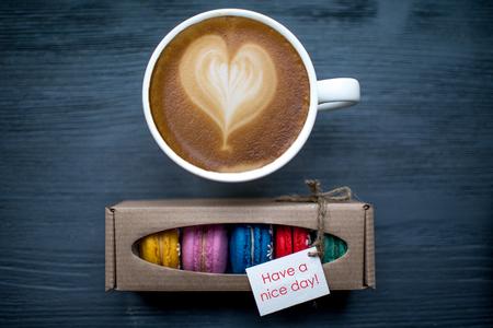Kopje koffie met hart vorm en bitterkoekjes koekjes op de donkere houten tafel