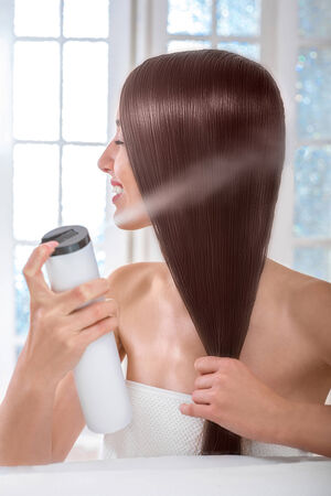 cabello lacio: Preciosa modelo de mujer caucásica hermosa con el pelo perfecto uso de spray para el cabello en una toalla en el salón de spa con ventanas en el fondo Foto de archivo