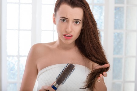 alopecia: Shocked young woman combing hair with comb in the bathroom. Hair loss