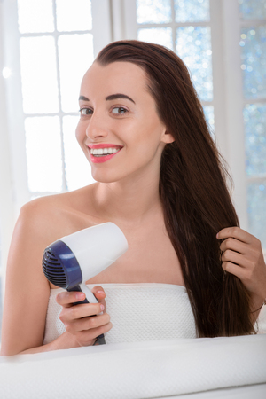 Young woman with long and dark hair drying hair with hairdryer in the bathroom photo