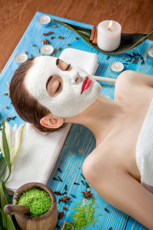 beaty: Young woman with spa facial mask on her face lying on blue table with flower, candles and sea salt in the beaty salon Stock Photo