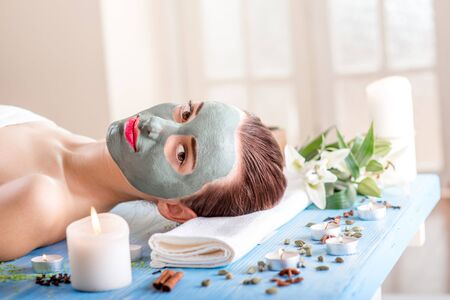 medical mask: Young woman with spa facial mask on her face lying on blue table with flower, candles and sea salt in the beaty salon. Side view Stock Photo