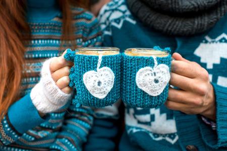 mujer tomando cafe: Pareja celebración de tazas de café de punto vestido con suéter