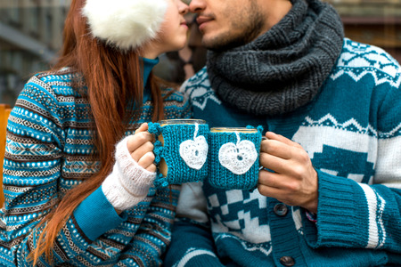 Couple holding knitted coffee cups dressed in sweater 스톡 콘텐츠
