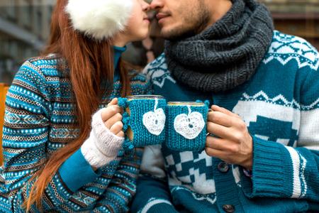 handkuss: Paar, das Strickkaffeetassen in der Strickjacke gekleidet