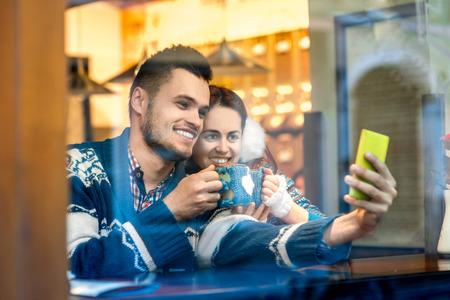 Young loving couple dressed in blue sweater sitting with knitted coffee cups and making selfie photo at the cafe in winter photo