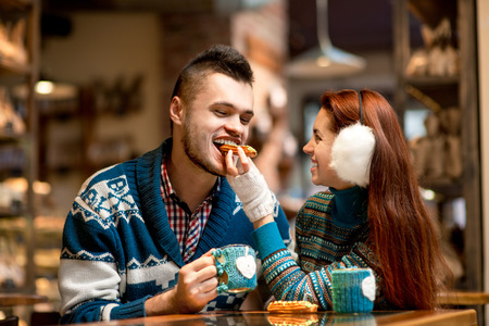Young loving couple dressed in blue sweater sitting with knitted coffee cups in the cafe in winter photo