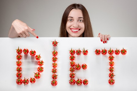 Woman pointing on white billboard with writing word DIET over grey background in studio photo