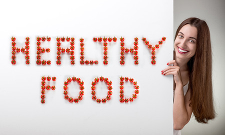 Woman pointing on white billboard with writing HEALTHY FOOD over grey background in studio photo