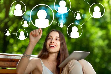 Jeune femme à ajouter des amis dans les médias sociaux avec tablette numérique dans le parc Banque d'images