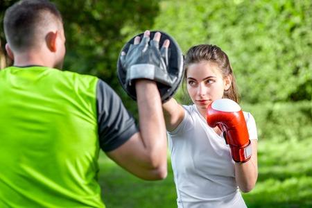 Jeune couple entraînement sportif à la boîte dans le parc Banque d'images