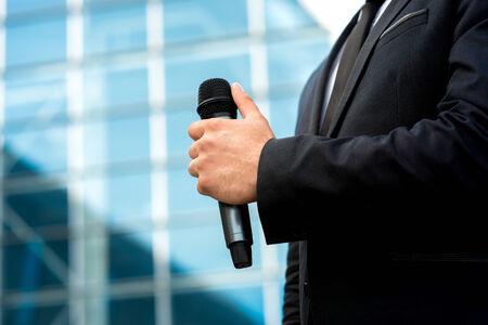 Man met microfoon in de hand op blauwe achtergrond contempopary