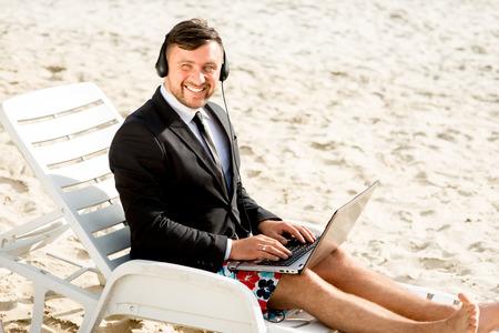 pantalones cortos: El hombre de negocios vestido con traje y pantalones cortos con videollamada con el portátil en la tumbona en la playa
