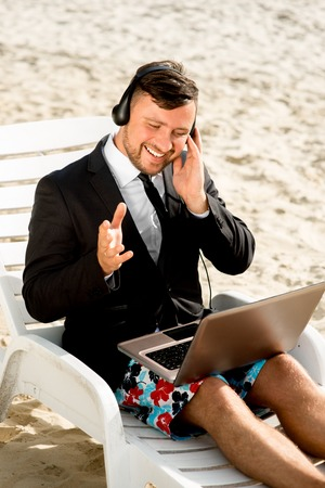 Businessman dressed in suit and shorts having video call with laptop on the sunbed at the beach