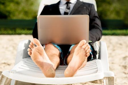 Zakenman gekleed in een pak en korte broek werken met de laptop op de zonnebank op het strand